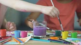 guache : Painting lessons at children art club. Kids putting paintbrush into water glass