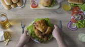 culto : Man addicted to unhealthy eating putting fried chicken on table, love for food