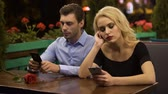 disinterest : Two young people boring on date, using smartphones, problems in relationship