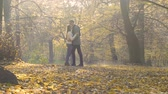 heterossexual : Young couple tenderly hugging in autumn forest, romantic gesture, people in love