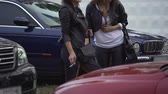 lungs : Two slim women smoking cigarettes on parking lot next to club, girltime break Stock Footage