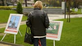 introducing : Woman looking at photography exhibit in park, openair gallery, country landscape