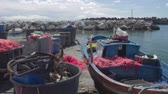 припаркован : Fishing boat parked near pier, drift nets lying in baskets, small business