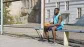 perdente : Sad Afro-American male sitting on the bench and playing ball, loneliness