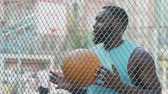 дриблинг : African American man waiting friends at basketball court to play game together