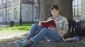 fascinante : Guy finishes reading book chapter, thinking about story sitting in shade of tree