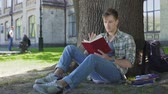 enredo : Male student skimming through pages of textbook, repeating learned material Vídeos