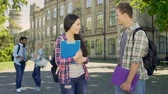 carefully : Handsome senior student flirting with beautiful asian girl on college campus Stock Footage