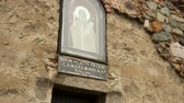 болгарский : Icon of Saint Petka above entrance door to church, cobblestoned path in front