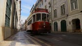 bonde : Small red tram arriving at stop in order to pick up people, urban transportation