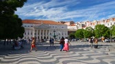 avlu : Many tourists walking through Rossio Square enjoying fountain and funny pigeons