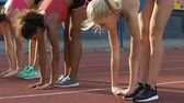 multirracial : Multiracial students leaning forward stretching legs, doing exercises at stadium