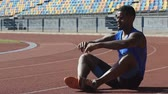 warming up : Strong athlete sitting on running track doing warmup and flexibility exercises