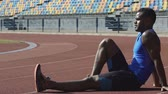 cansado : Sportsman resting on racetrack observing training of competitors, exercising