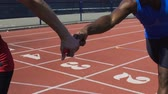 asa : Hispanic athlete passing baton to his teammate, relay run, track and field