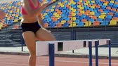 легко : Close-up view of girls easily jumping over obstacles, hurdle race, competition Стоковые видеозаписи