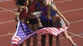 troféu : USA sports team holding flag of country, hugging and smiling celebrating victory Stock Footage