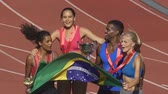 bandiera brasiliana : Happy athletes jumping with Brazilian flag rejoicing victory, sports competition
