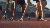 спринт : Close-up of young female athletes preparing to run at starting line, slow-motion