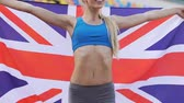 troféu : Joyful sportswoman enjoying victory in sports competition and holding UK flag