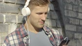 escuta : Handsome young man in headphones smiling, looking at smartphone screen, chatting