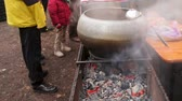 needy : Refugees warming themselves near fire and waiting hot soup preparing for dinner
