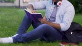 eğlenceli : Multiethnic man sitting on grass reading book, recreational activity, bookworm Stok Video