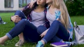 поддерживающий : Best female friends sitting on grass, one hugging another by shoulder, support