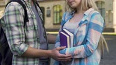 timid : Guy flirting with girl taking her by arms, girl being shy, university love, date Stock Footage