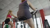 motivováni : Woman with thick legs pedalling on stationary bike in the gym, weight loss