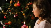 making a wish : Child blowing out decorated Christmas candle and making a wish, magic moments