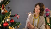 iyi bir ruh hali : Happy little girl dancing with sparkler near Christmas tree at home, celebration