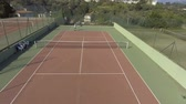 çiftler : Red-haired woman playing tennis with her boyfriend, aerial view of court Stok Video