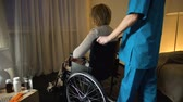ošetřovatelství : Medical worker bringing depressed old woman in wheelchair to room, loneliness