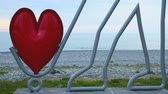 batumi : Creative statue of man with heart in Batumi, teen friends having rest at seaside Stock Footage