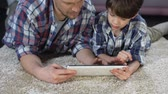 интерактивный : Dad and his son learning how to use new tablet, modern technology, closeness