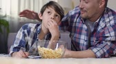 Father hugging little son during watching film home with popcorn, proud of child
