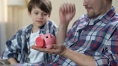 Father and son putting coin into piggy bank and giving high five, save for dream