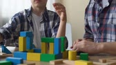 беспорядок : Mentally retarded teenager playing with cubes, volunteer looking after him.
