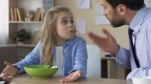 forcing : Strict father shouting at daughter, forcing to eat, demanding man scolding child Stock Footage