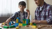 oyun zamanı : Father and serious son playing with toy cubes, building house together, leisure Stok Video