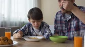 kukoricapehely : Pleased son and father eating tasty cornflakes at breakfast, morning tradition