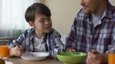 kukoricapehely : Father and son having breakfast together, eating tasty cornflakes morning home