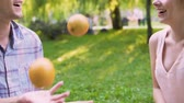 gastos : Man juggling oranges and girlfriend applauding, spending time together in park Vídeos