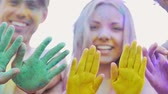 hélio : Happy friends waving hands painted in colorful powder, gesturing hello, party