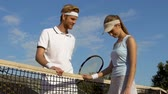 antreman : Male tennis player talking to beautiful woman after match at sports complex