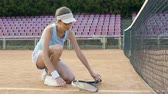 tkanička : Cute female tennis player tying her sport shoes laces before starting match