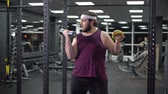間違った : Obese man holding dumbbell eating burger, refusing from doing sport, addiction 動画素材