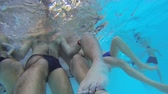 step by step video : Underwater camera taking video of lower bodies of people sitting on step in pool Stock Footage