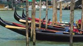 припаркован : Decorated gondolas swaying at pier, water taxi in Venice as tourist attraction